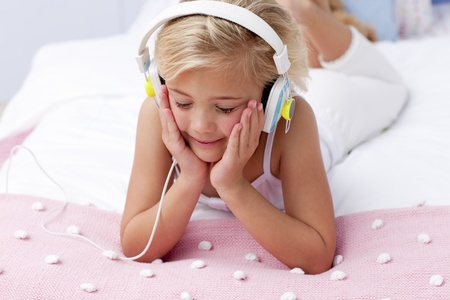 Little girl in bed listening to the music photo