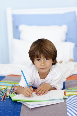 Portrait of little boy drawing in bed photo