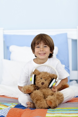 Happy kid playing with headphones and teddy bear photo