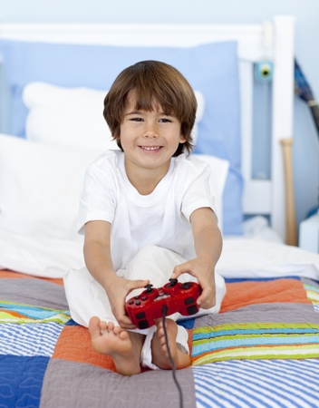 Boy playing videogames sitting in his bed photo