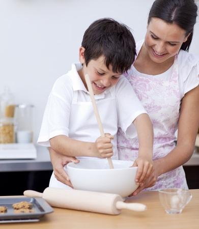 ni�os cocinando: Madre e hijo sonriendo en la cocina Foto de archivo