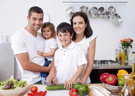 familia comiendo: Hijo de preparar la comida con su familia Foto de archivo