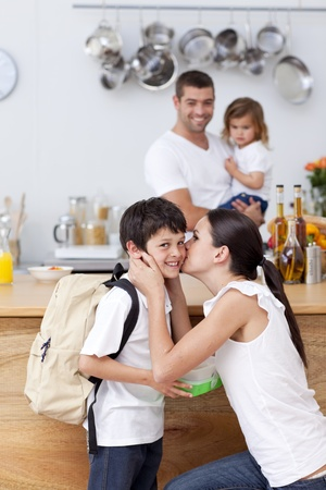 Mother kissing her son before school