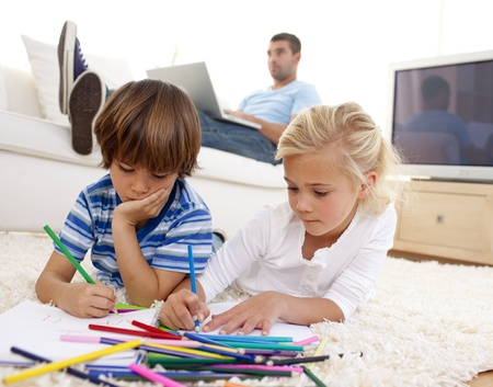 Children painting in living-room and father using a laptop photo