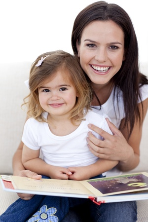 Smiling mother and daughter reading a book photo