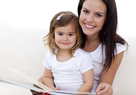 Portrait of mother and daughter reading a book photo