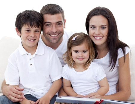 Portrait of a smiling family reading a book photo