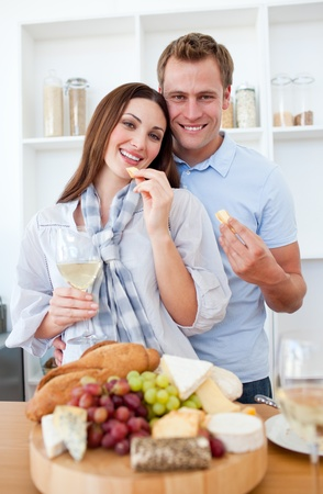 Cheerful couple drinking white wine and eating cheese photo