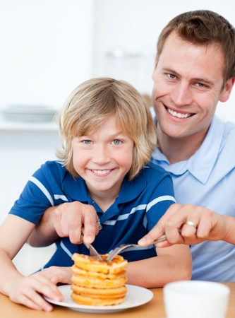 Smiling father and his son eating waffles photo