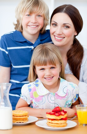 Cheerful mother and her children eating waffles with strawberries photo