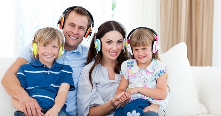 Smiling family listening music with headphones photo