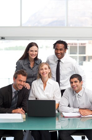 Smiling businessteam working together with a laptop Stock Photo - 10077080