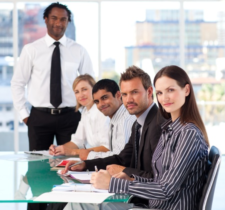 business model: Business people looking at the camera in a meeting Stock Photo