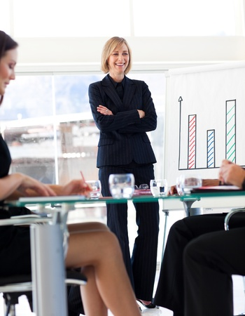 Attractive businesswoman smiling at her colleagues in a meeting Stock Photo