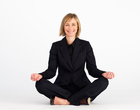 Mature businesswoman meditating on the floor photo