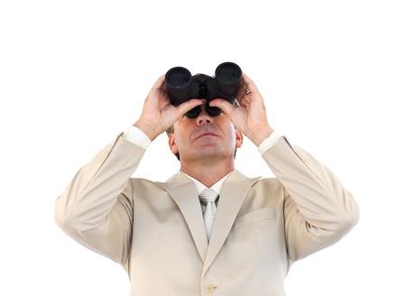Confident businessman looking through binoculars  photo