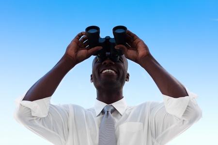 looking ahead: Businessman looking through binoculars