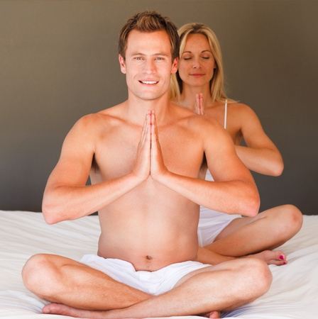 Young couple doing yoga on bed photo