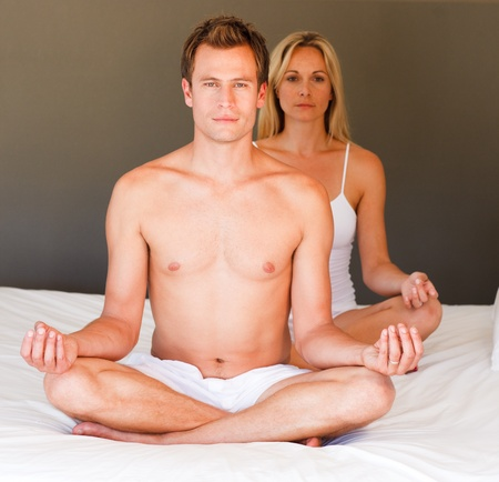 Couple doing meditating on bed photo