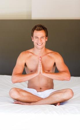 Smiling man meditating on bed photo
