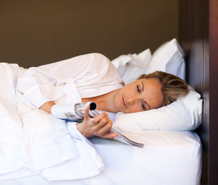Young woman reading a magazine in bed photo