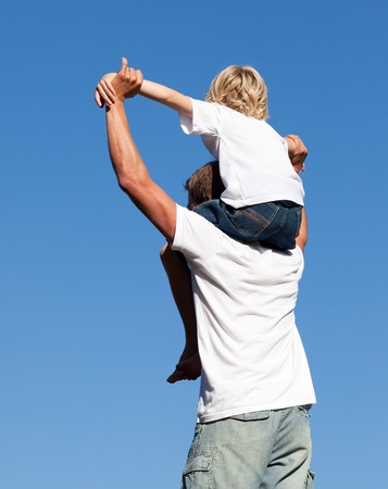 shoulder ride: Son sitting on his fathers shoulders