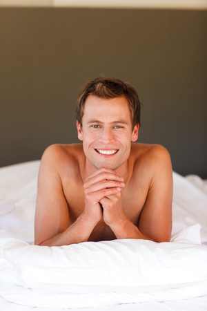 Smiling handsome boy lying in bed with copy-space photo