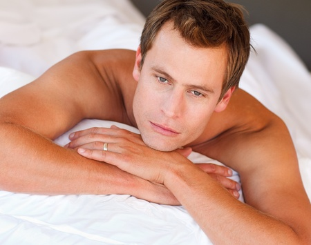 Young man lying in bed photo