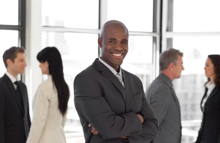 Happy business leader looking at camera in front of team Stock Photo - 10109611