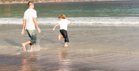 Father and son playing on a beach photo