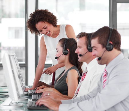 contact center: Afro-American manager checking his young team work Stock Photo