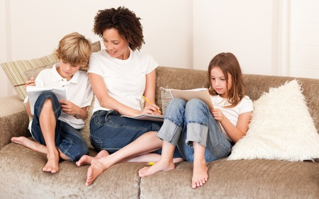 Charming family sitting on a sofa Stock Photo - 10077316