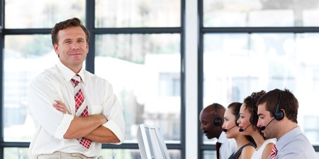 Senior manager with folded arms in a call center photo