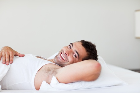 Handsome man lying in bed smiling photo