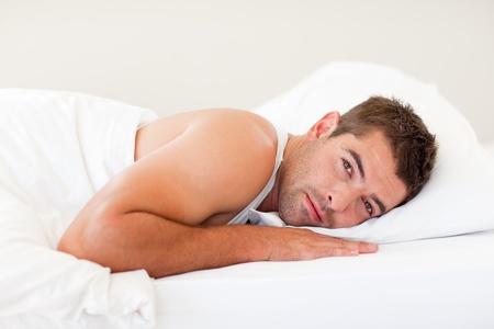 mid twenties: Handsome man lying in bed