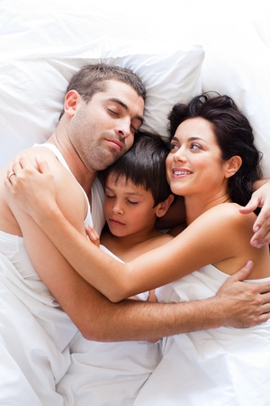 Happy family resting in bed  photo