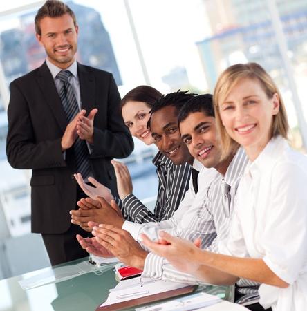 negocios internacionales: Aplaudiendo Internacional equipo de negocios en el final de una presentaci�n Foto de archivo