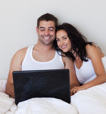 Attractive couple using a laptop on a bed Stock Photo