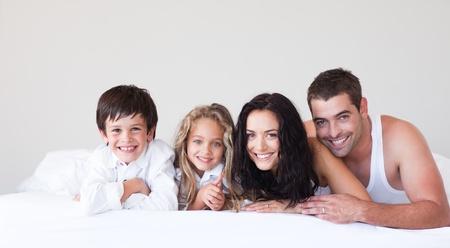 Joyful family lying on their bed photo