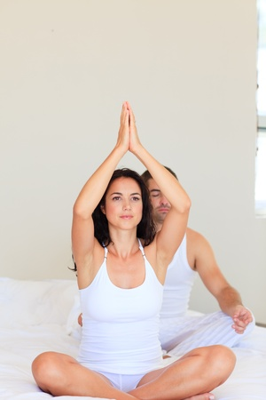 Couple practicing yoga in bed photo