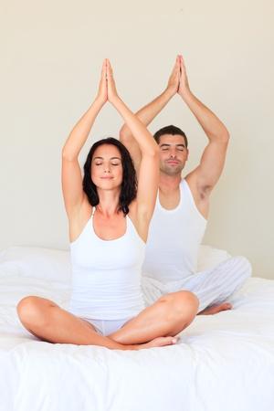 Couple sitting on bed practicing yoga photo