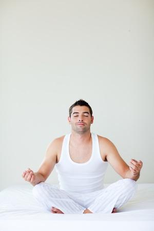 Man sitting on bed meditating photo