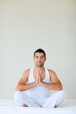 Young man doing yoga in bed with clossed eyes photo
