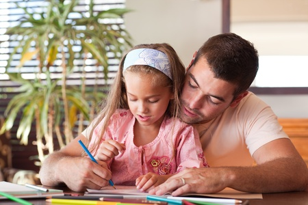Happy father helping her daughter for homework photo