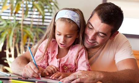 Delighted father helping her daughter for homework photo