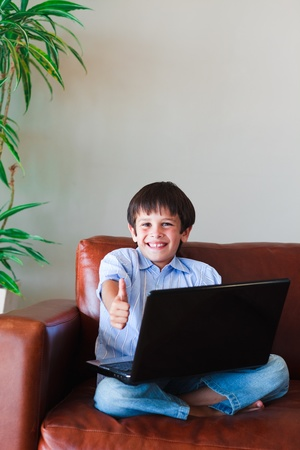 Kid using his laptop with thumb up Stock Photo - 10076547