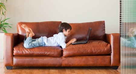 Kid playing with a laptop on the sofa photo