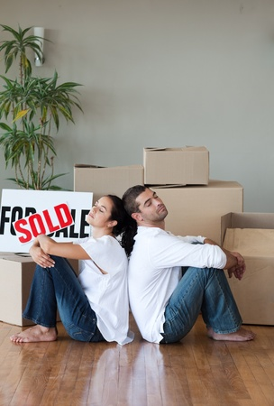 Smiling couple with unpacking boxes moving to a new house photo