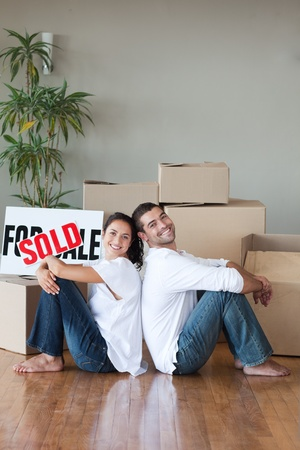 Cheerful couple with unpacking boxes moving to a new house photo