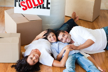 Smiling family in their new house lying on floor photo